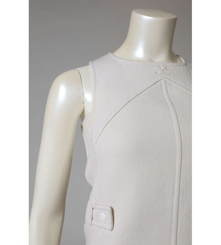 A classic piece of the 1960's tailoring by the master of modernism, André Courrèges. This ivory wool jumper dress is a nice example of pure Sixties chic. Side elasticated snap-belts create a fitted look even with this iconic A-line construction.