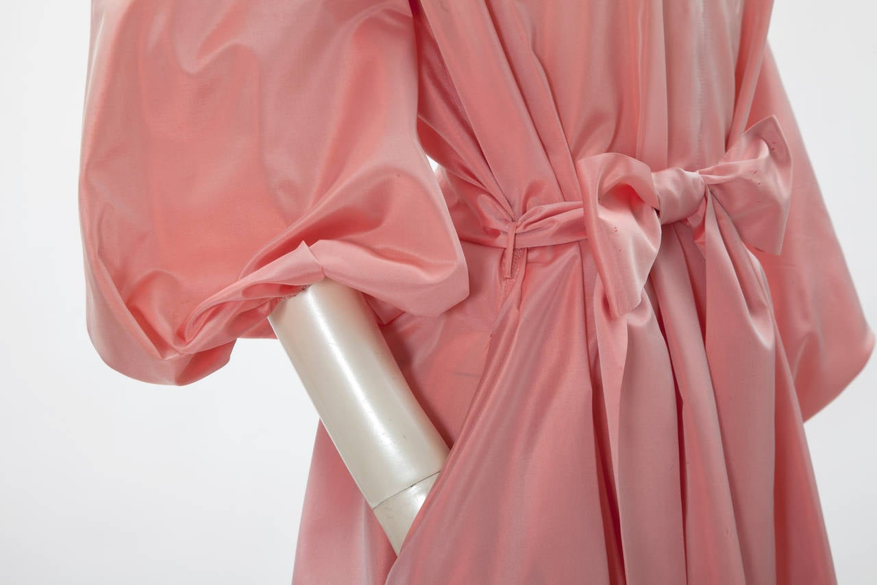 Late 70's, early 80's YSL silk taffeta tent gown with fabric-matched belt. This evening dress is delicately gathered at front and back of the shoulders. Voluminous puffy long sleeves finish into an elastic cuff. Refined invisible side pockets.
