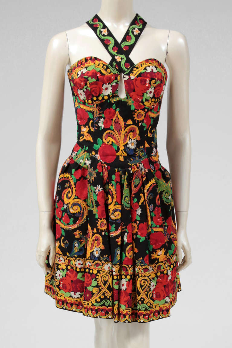 Amazing 1980's print cotton dress by Christian Lacroix. With an exuberant and colorful vibrant print, the dress has also a black tulle petticoat which provides more volume to the skirt. The back of the dress has oversized corset details with large