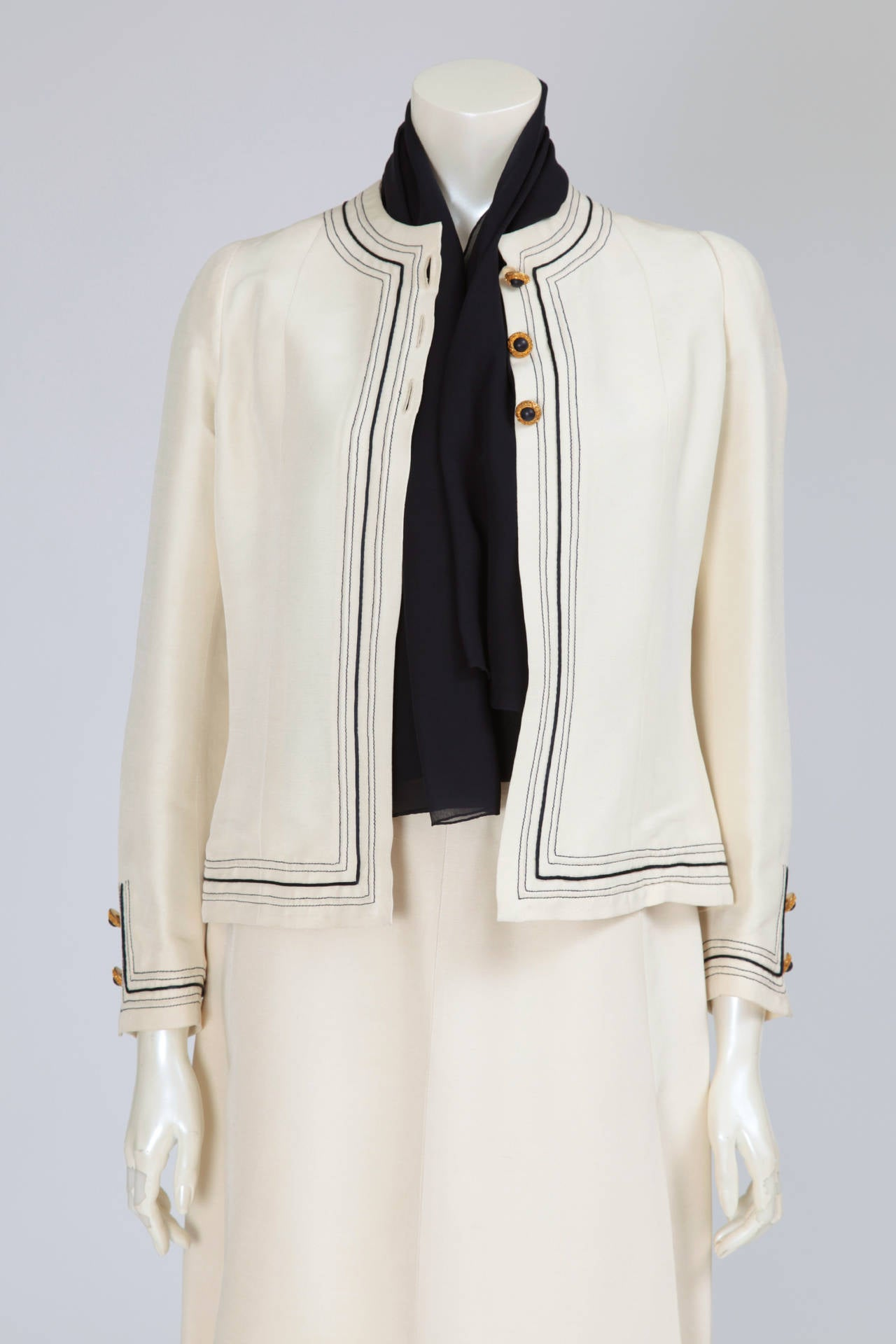 A refined classic skirt suit, labelled and numbered n° 48765 and n° 48767. This timeless piece of Chanel haute couture is composed of a jacket, a skirt and a blouse. The blouse is made of dark blue silk chiffon, with an optional tie, while the