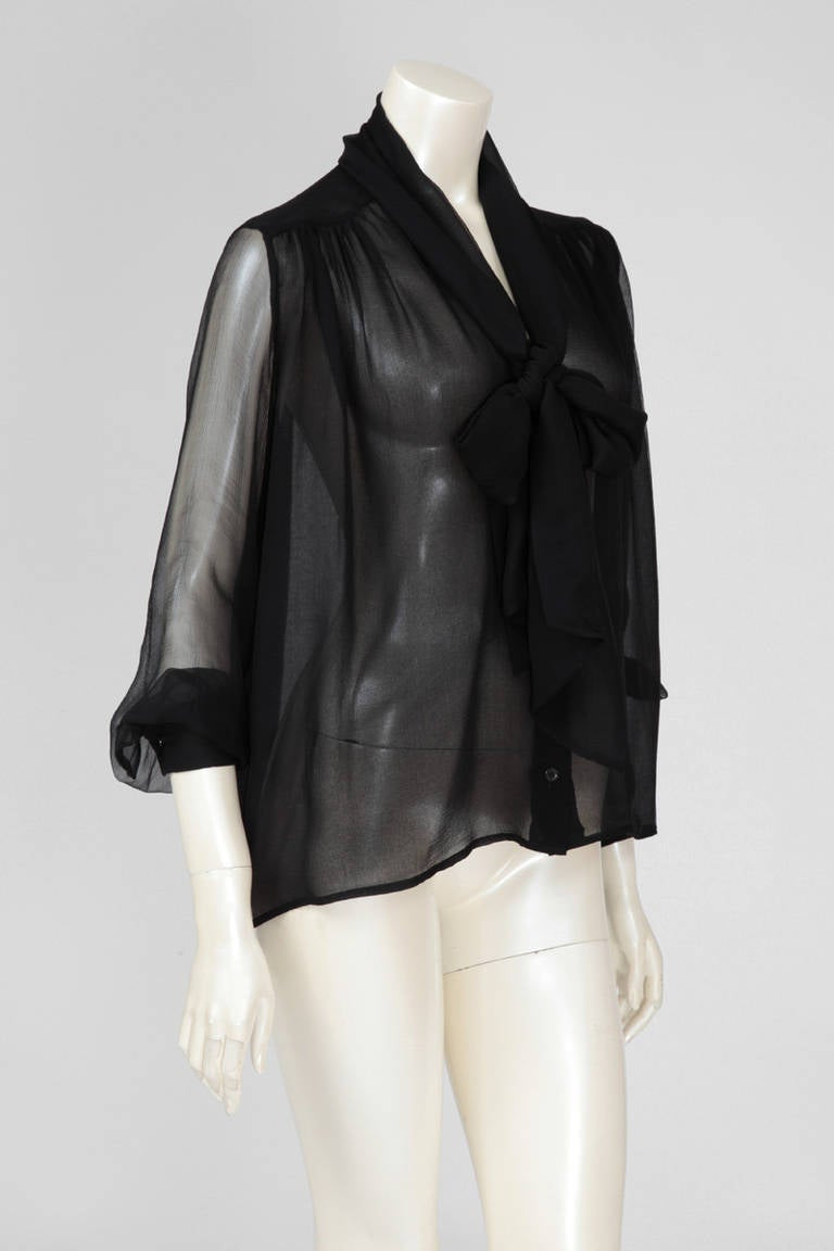 "From the master of the effortlessly chic blouse, this garment is made of the utterly soft and delicate black ""crêpe georgette"" silk. Fabric is doubled on the body, single layered on the arms. Scarf ties and blouse buttons down the front. 