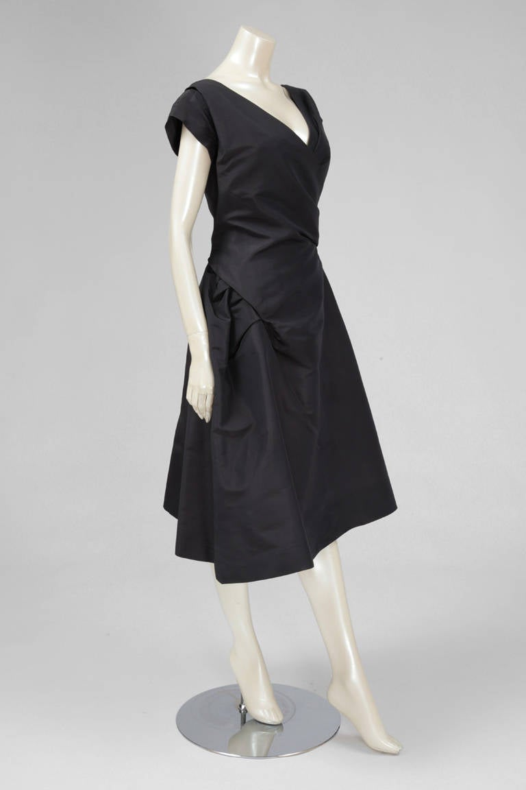 """Simply Dior. This late 50's (c. 1958) numbered (03510) cocktail dress is an exquisite example of the """"élégance à la française"""" expressed by Christian Dior. Constructed in dark grey silk taffeta, the volume of the skirt emphasize the small waistline."""
