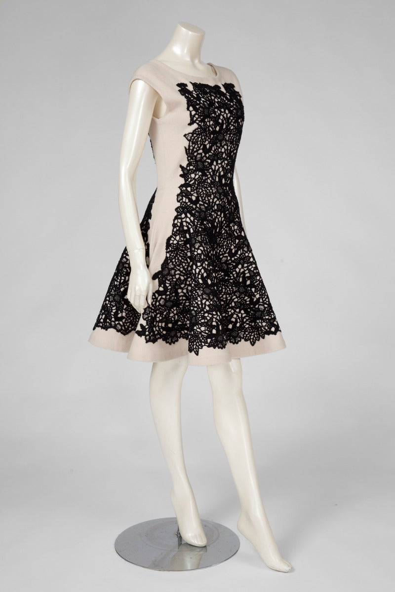 Fantastic Christian Dior skater dress from the 2012 fall-winter collection. Constructed in light beige wool and cashmere, the dress features a beautiful black guipure lace over the front and the back. Hidden zip closure on the left side. Unlined.
