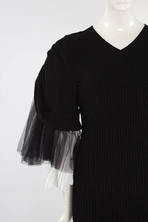 Runway Chanel black ribbed stretch mini dress (look 38 -> see picture 11) with white pleated knit and black tulle. Three-quarter length tiered ruffle raglan sleeves. The unlined dress features a V-neckline and closes with a zip at the back. Tagged a