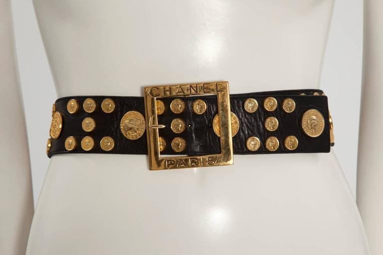 Very rare 90's Chanel piece, featuring coins of different sizes on a large black lambskin belt. Ten big coins picture various Chanel symbols (for example the ear of wheat, the double C or the Chanel n° 5 flask). The small coins feature Coco Chanel's