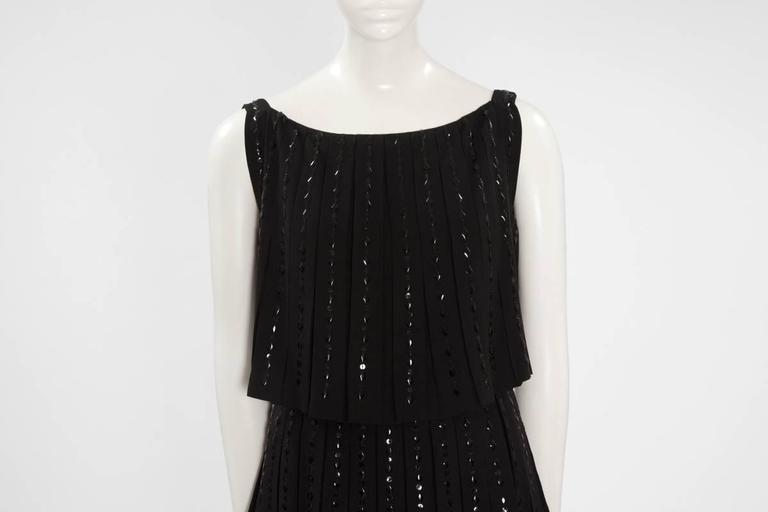Late 60's Norman Hartnell couture beaded black wool cocktail dress made of three pleated tiers falling in a graceful cascade. Embellished with beautiful black diamond-shape and black round sequins, the dress closes with a zip, a hook and nine tiny