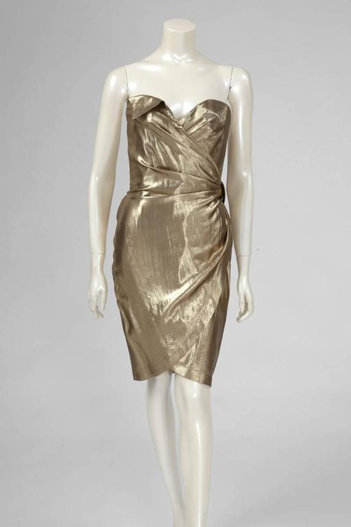 Late 80's - early 90's Thierry Mugler lamé strapless wrap dress with adjustable polished pewter buckle above the left hip closing a pleated belt. The dress is fully lined and the bodice is strengthened. Labeled a French size 38 (US 4-6), this piece