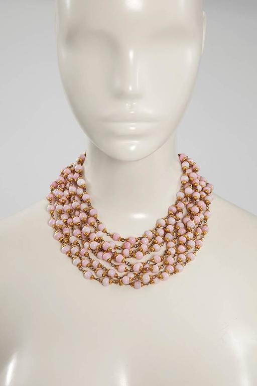 Mixing a ladylike effortless elegance with modern edge, this 1993 Chanel necklace has nine strands of faux Angel skin coral glass beads on gold-tone brass chains. An adjustable hook customizes the length. 