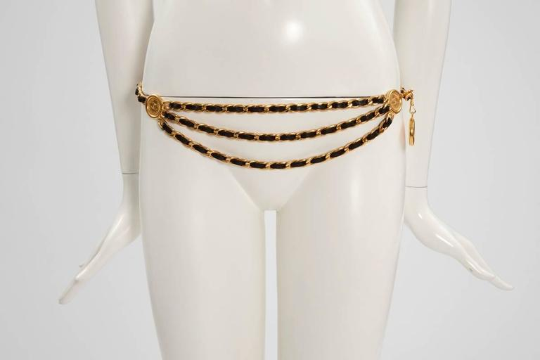 "Early 90's Chanel triple gold plated chain waist belt with black lambskin leather woven throughout. Large ""CHANEL 31 RUE CAMBON PARIS"" medallions. Hook closure. Perfect for layering over a skirt, skinny jeans or leggings, this piece can be also worn"