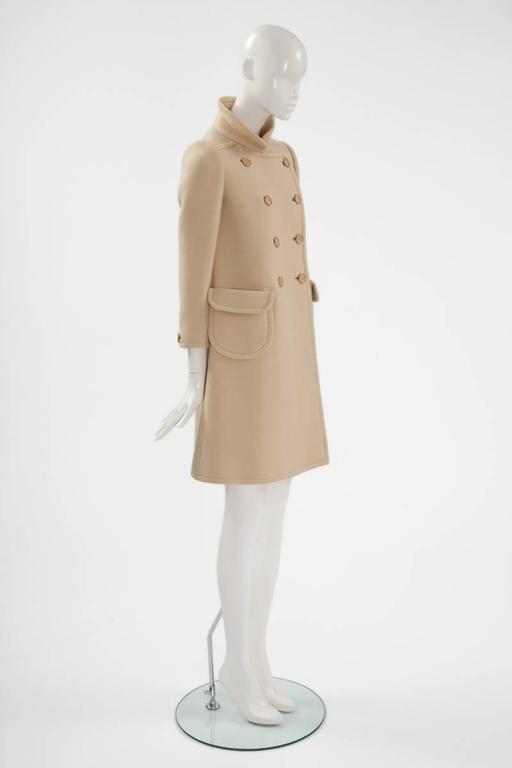 This wonderful numbered Courrèges haute couture coat is a fantastic timeless piece for spring, autumn and winter. Constructed in light beige wool gabardine, the classic 60s cut creates a flattering A-line silhouette. Featuring a Peter Pan collar,
