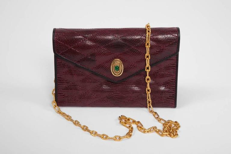 Unusual vintage Chanel bag in garnet red lizard skin and black leather piping, embellished with an elegant green Gripoix glass medallion adorning the flap. Its single strap is crafted in a textured gold link chain. Snap closure. Matching garnet red