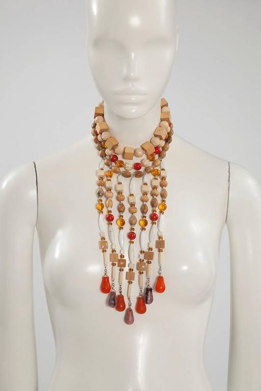 Very rare unusual multi strand necklace recalling certain designs of the dresses from the YSL 1967 haute couture African collection. Crafted with wood, various stones (red jasper and white marble-like), glass, molten glass and rhinestones of