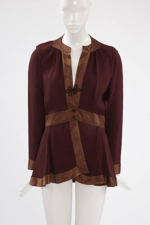 Ossie Clark shirt-top from the seventies, very representative of his design featuring a beautiful contrast between the dark brown matte moss crepe body and the satin details. The unlined top closes with a brandeburg knot and two covered buttons. The