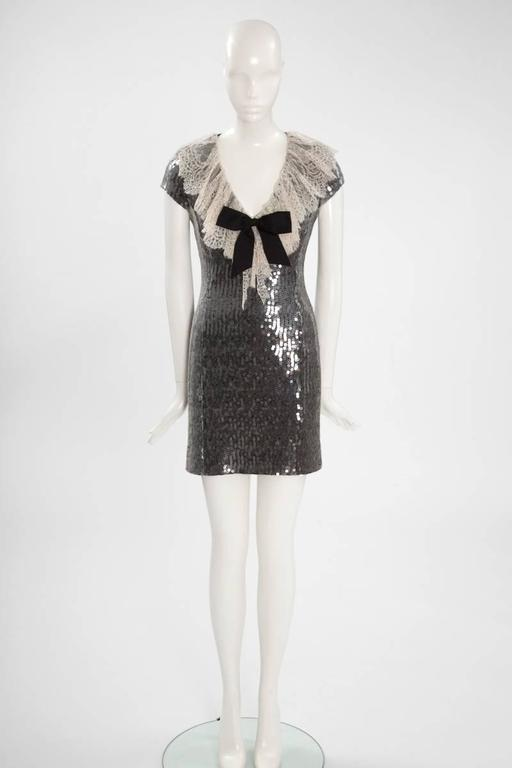 A marvellous choice for evening events, this rare Chanel circa 1987 figure-skimming mini dress is made from black silk georgette and embellished with hundreds of transparent sequins that catch the light from every angle. Chantilly lace collar and