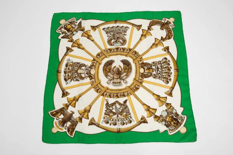 This bold white carré with golden Egyptian symbols was designed by a favourite Hermes artist, Caty Latham. First issue in 1970, this silk twill scarf has been reissued in 1999. Original Hermes box not included.  Dimensions : approx. 90 x 90 cm
