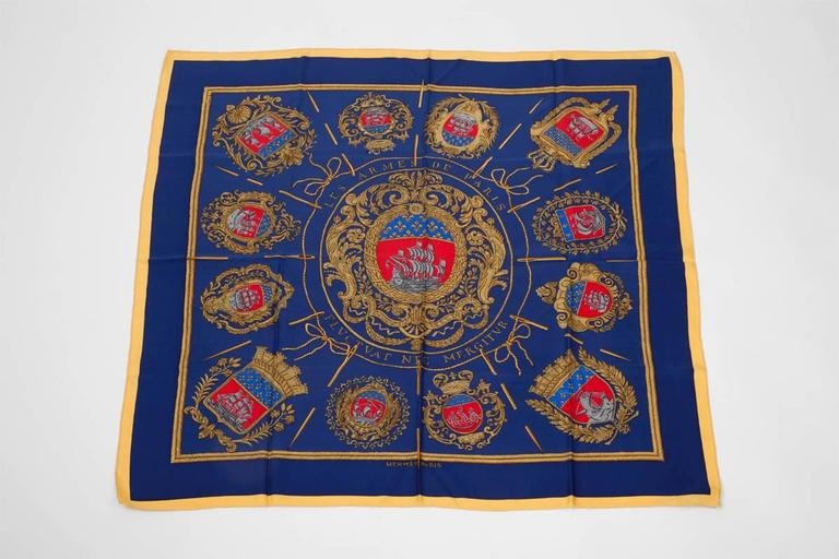 Hermes « Les armes de Paris » silk twill carré scarf. Designed by Hugo Grygkar, this rare 100% silk elegant scarf features a print of the traditional Paris coats of arms on a navy blue background. First issued in 1954, it was reedited only in 1989