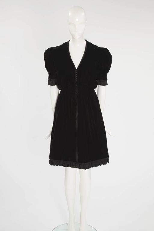 """Perfect for everything from cocktail parties to dinners, this wonderful 60's Jean Patou """"little black dress"""" has a """"dirndl"""" feel. Constructed in black velvet, the dress features puffed shoulders and a ruffled mate silk taffeta around the sleeves and"""