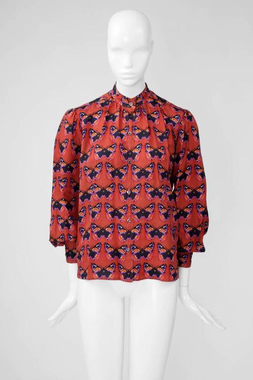 Very rare 70's burnt orange YSL refined natural silk stand-up collar blouse. Unusual colorful butterfly print. Labelled a French size 38 (US 4-6), the blouse runs a bit small to size.   Fits approx. : US 2-6 / FR 36-38   Measurements (taken flat)