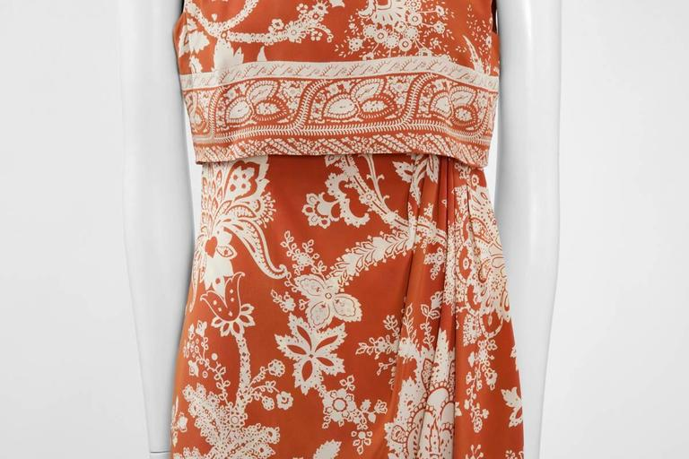 Constructed in rust silk with an ivory paisley pattern, this early 90's Valentino dress is draped on the left side and features a high neckline. Giving a two pieces illusion, it fastens in two steps : the dress is zipped at first along the back,