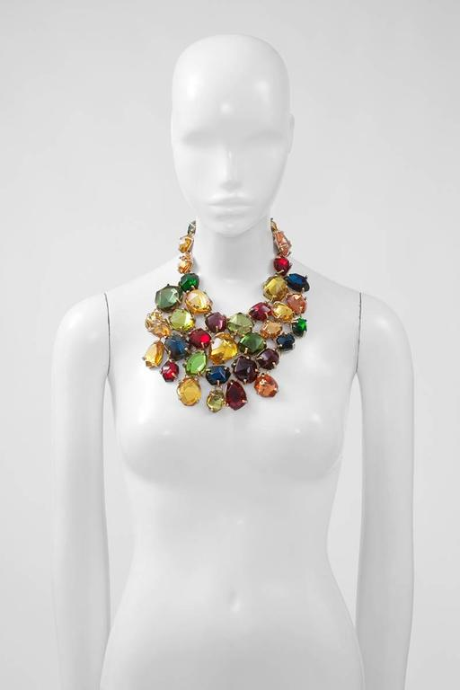 "Dramatic Yves Saint Laurent gilt metal bib necklace with irregular large bright multi-colored resin stones in clawed settings. Hook and eye closure at the back. The length of the necklace is adjustable and features the ""YSL"" logo tag (see"