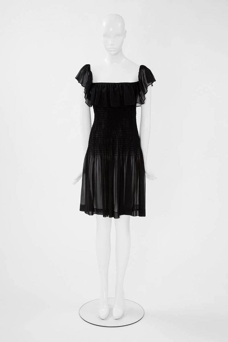 Constructed in black silk chiffon, this 70's YSL dress is entirely smocked from shoulders to hips. It features a soft ruffle collar over the bust and back, which can be worn off or on the shoulders. Subtly sexy with its transparency, this unlined