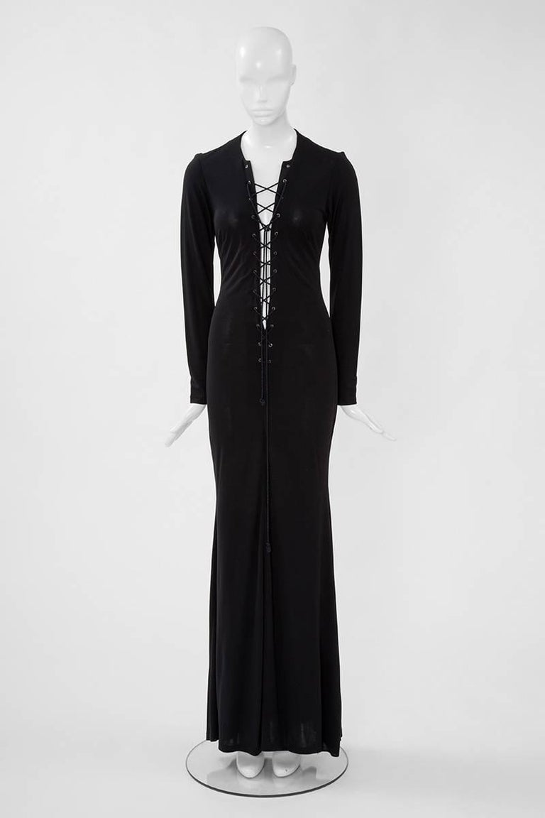 Reminiscent of the iconic saharienne, this YSL black lace up jersey maxi dress could be incredibly sexy ! Enhancing graciously the feminine silhouette, just slip on to wear this versatile piece. This very dress was used for the official shooting