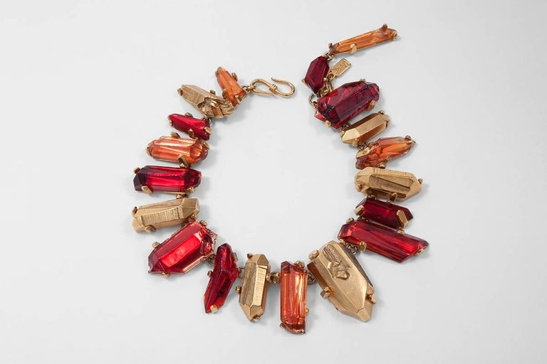 """This gilt metal Yves Saint Laurent chunky necklace features irregular faux red quartz resin crystals set in ostensible faux gold claws. Hook and eye closure at the back. The length of the necklace is adjustable and features the """"YSL"""" logo tag (see"""