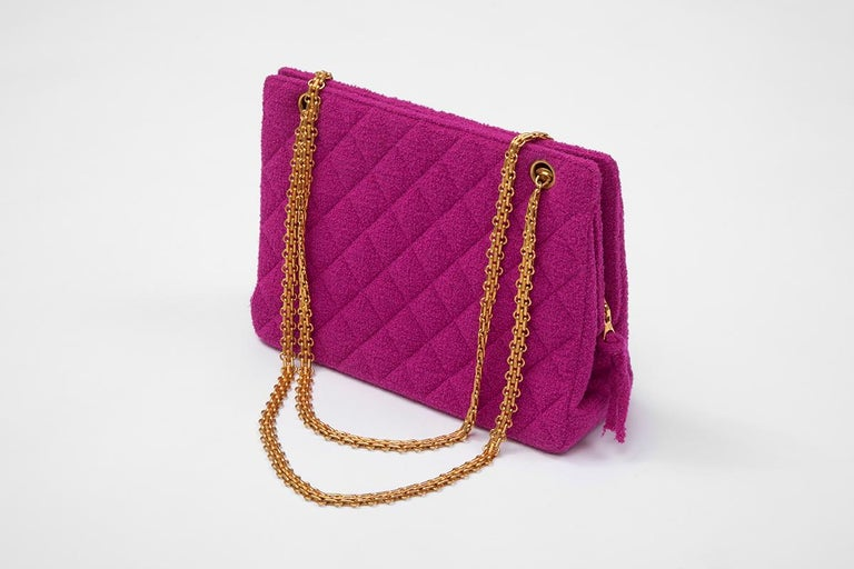 From the iconic SS1994 runway collection, this hardly worn Chanel shoulder bag is crafted from bright fuchsia « bouclé » tweed and features gold hardware. Fully lined in a refined matching « gros-grain » silk, this structured piece has two interior