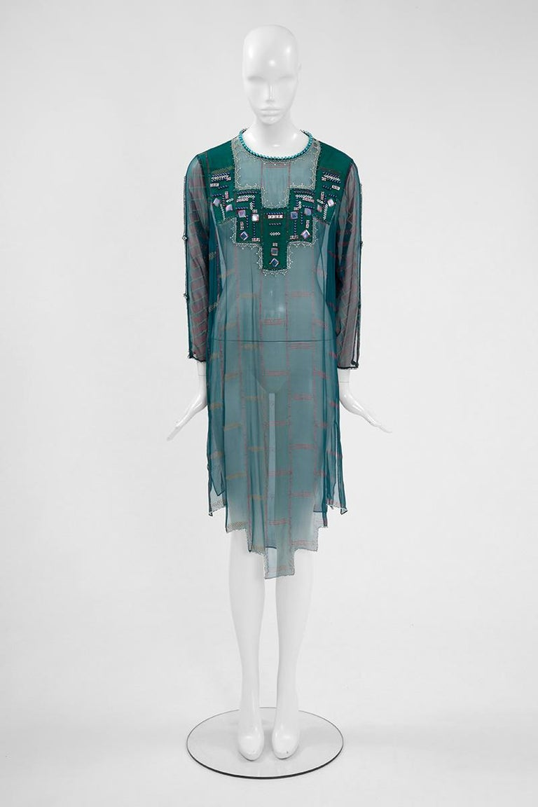 Constructed in sheer bottle green hand painted silk chiffon, this tunic dress will be perfect for a summer lunch by the pool. It has a round neckline that's framed with matching beads. Hand-embroidered sequins, beads and strass embellish the chest,