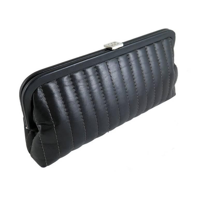 The mademoiselle clutch was a seasonal item and was never reproduced again. This piece is well kept and in excellent condition. Features black lambskin leather exterior and black camellia fabric interior. There is an inner slot pocket. Silver CC