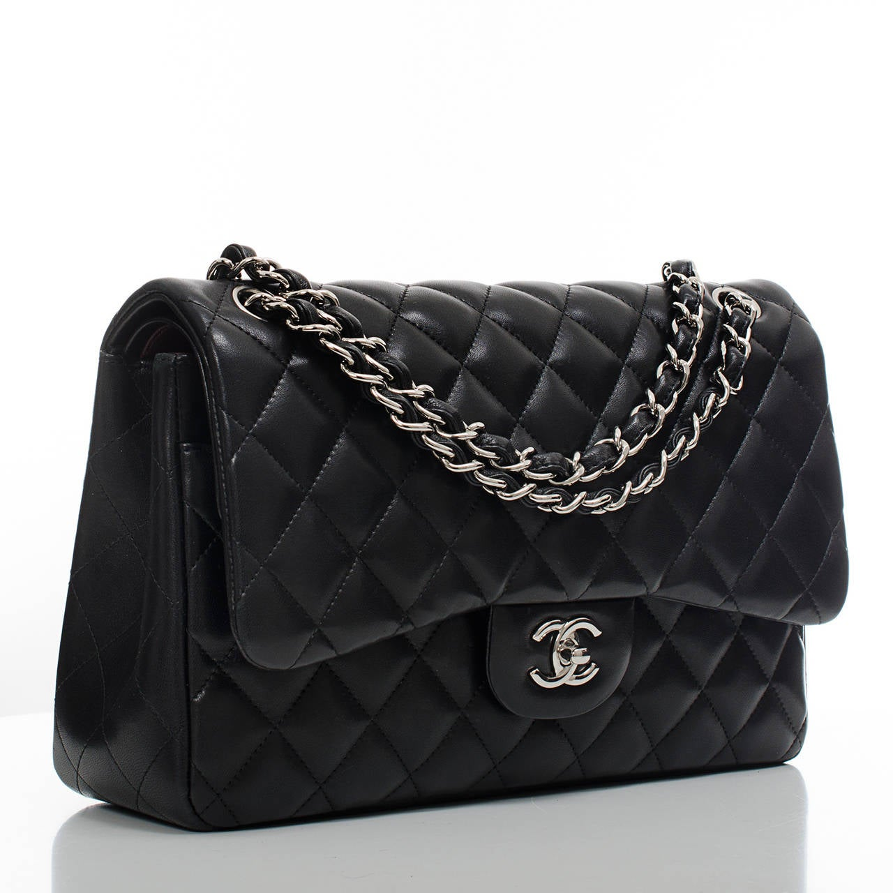 Chanel black Jumbo Classic double flap bag of quilted lambskin leather with silver tone hardware.  This Jumbo Classic double flap of black lambskin features a front flap with signature CC turnlock closure, half moon back pocket and an adjustable