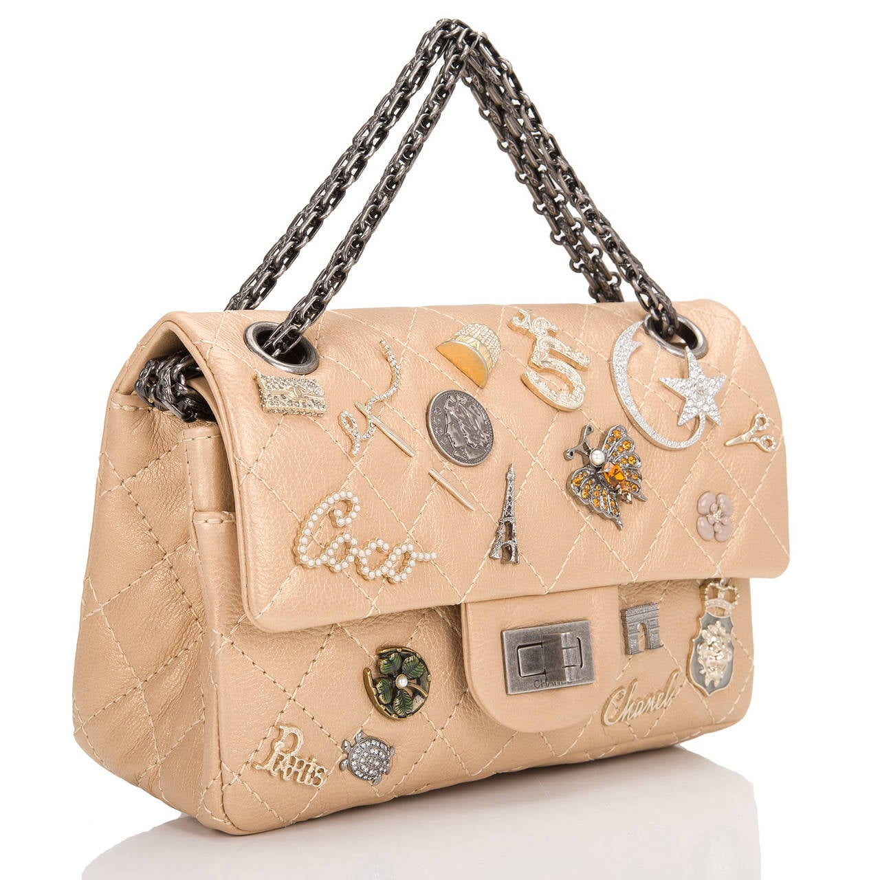 This Limited Edition Chanel Lucky Charm Reissue 2.55 bag in gold aged calfskin leather with aged ruthenium hardware in size 224. This embellished Chanel bag features 21 iconic Chanel charms, front flap with Mademoiselle turnlock closure, a half moon