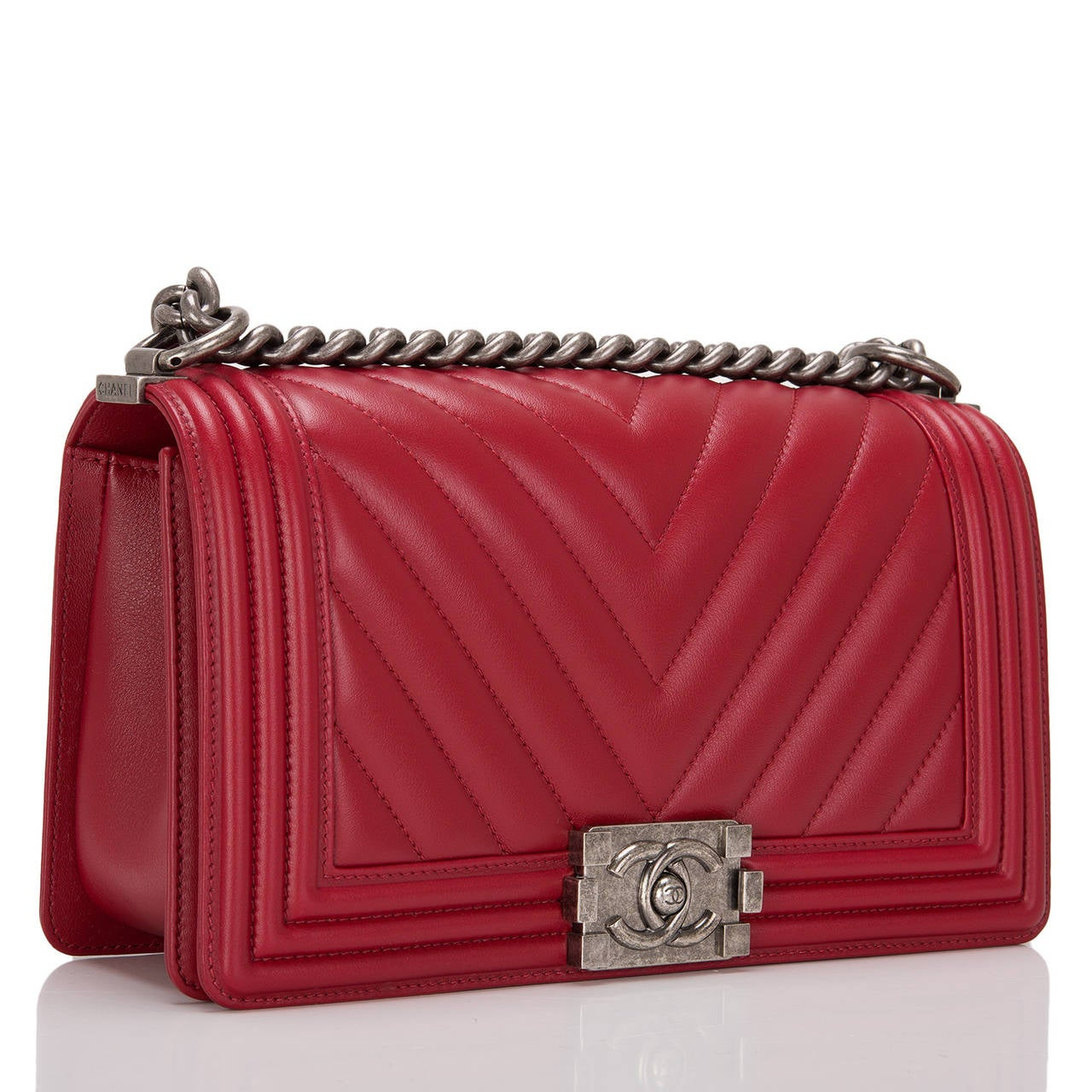 This Chanel red Chevron Medium Boy bag features beautiful red quilted chevron calfskin and aged ruthenium hardware. This Chanel bag is in the classic Boy style with a full front flap with the Boy signature CC push lock closure detail and aged