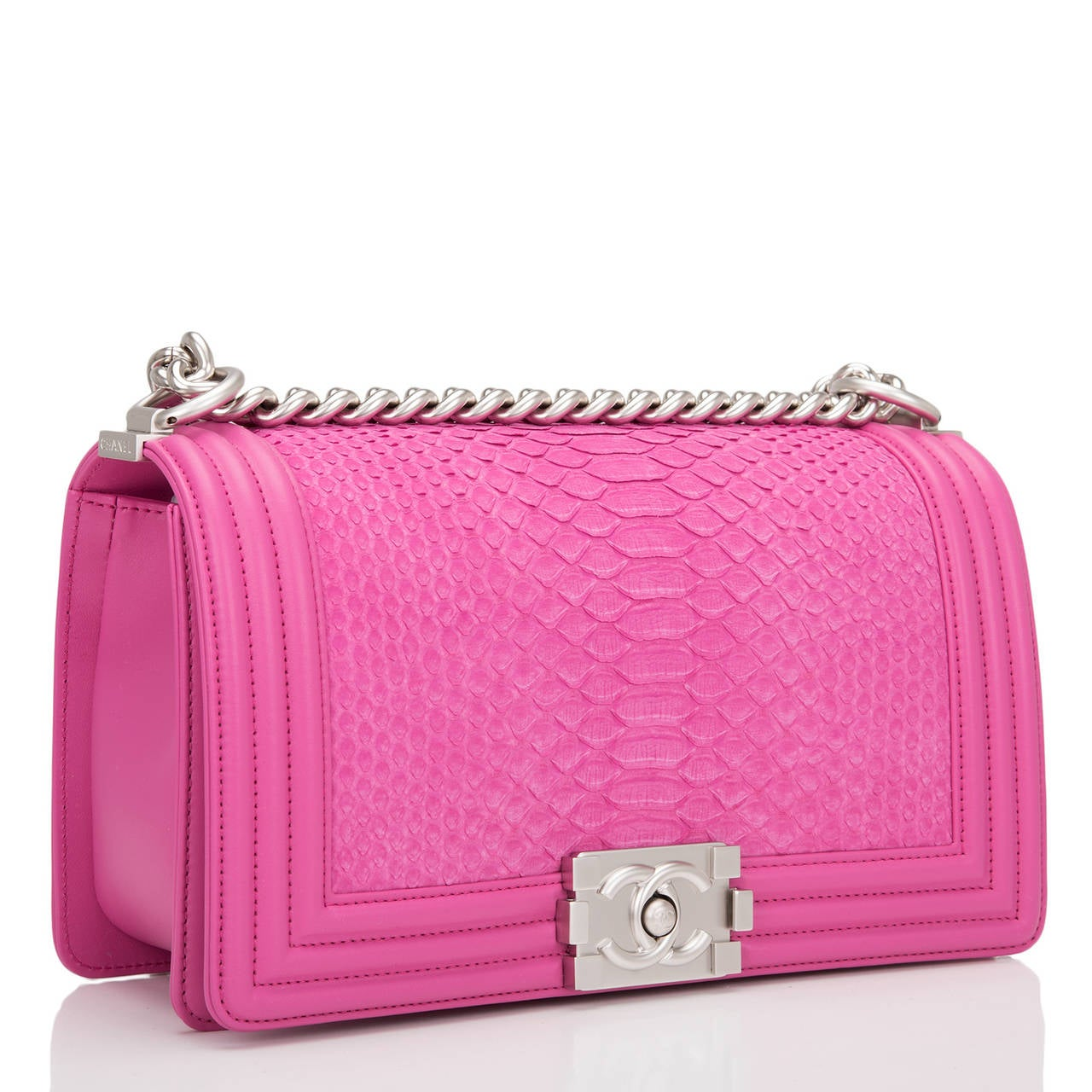 This Chanel pink python Medium Boy bag features beautiful pink python skin and matte silver tone hardware with pink lambskin trim. This Chanel bag is in the classic Boy style with a full front flap with the Boy signature CC push lock closure detail