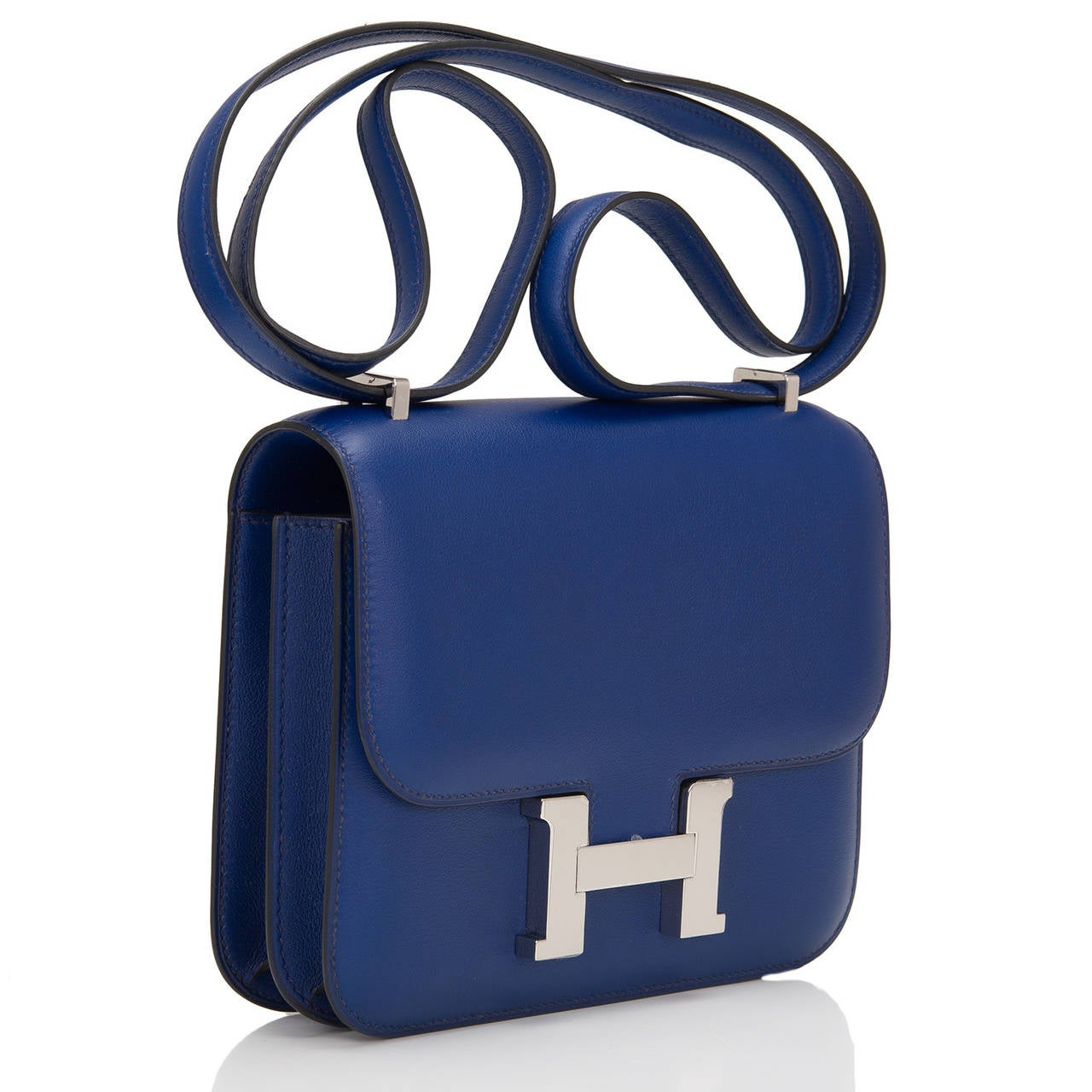 "This classic Hermes Mini Constance 18cm in Blue Sapphire swift leather with palladium hardware features tonal stitching, metal ""H"" snap lock closure and an adjustable shoulder strap.