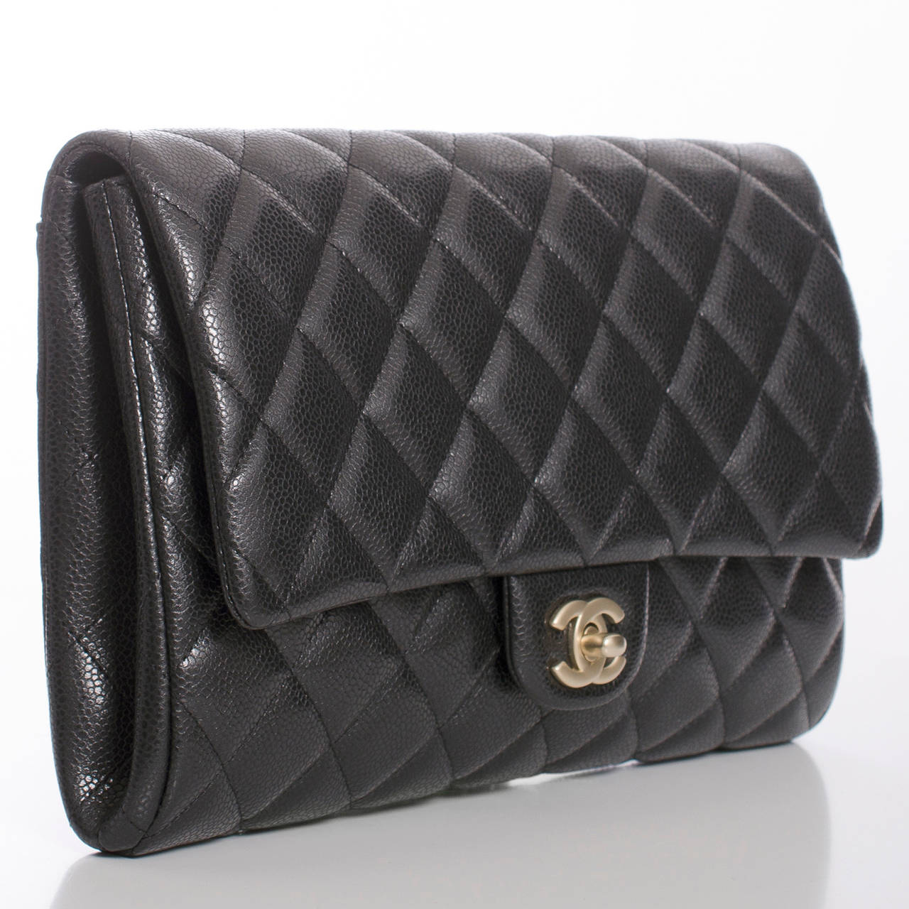 Chanel New Clutch With Chain of quilted black caviar leather with matte gold tone hardware.    This bag features CC turnlock closure, a rear envelope pocket, and interwoven gold tone chain link with black leather shoulder strap which can be tucked