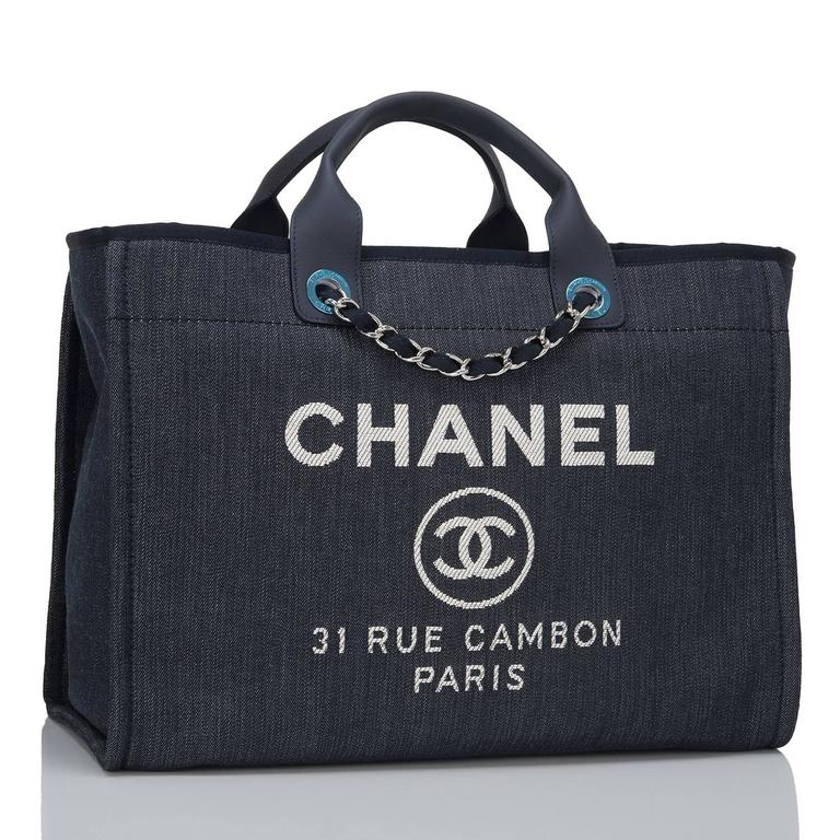 """Chanel large Deauville shopping tote 30cm of dark blue denim with silver tone hardware.  This bag features Chanel logos and the street name of Chanel's famous flagship store, """"31 Rue Cambon Paris"""" printed on the front, calfskin top handles, and"""