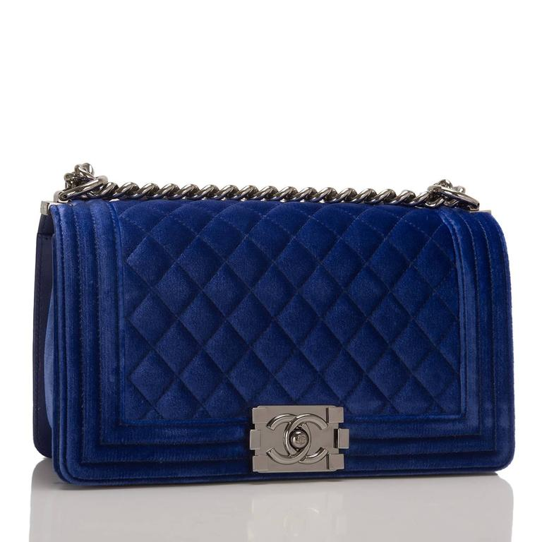 Chanel Medium Boy bag of blue velvet with ruthenium hardware.  This bag features a front flap with Le Boy CC push lock closure and a ruthenium chain link with blue leather padded shoulder strap.  The interior is lined in blue fabric with an open