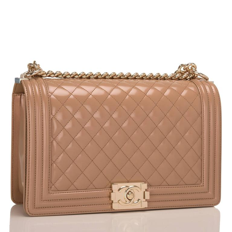 Chanel New Medium Boy bag of dark beige iridescent calfskin leather with light gold tone hardware.  This bag features a full front flap with the Le Boy CC push lock closure and a light gold tone chain link and dark beige leather padded