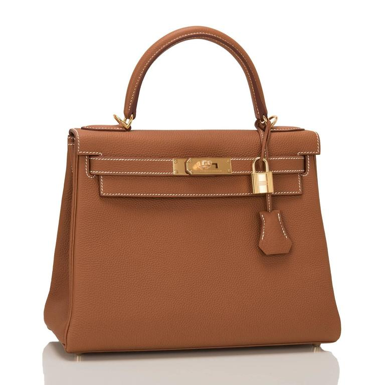 This Hermes Gold Kelly 28cm in togo leather with gold hardware.  It features white contrast stitching, front toggle closure, clochette with lock and two keys, single rolled handle and optional shoulder strap.  The interior is lined in gold