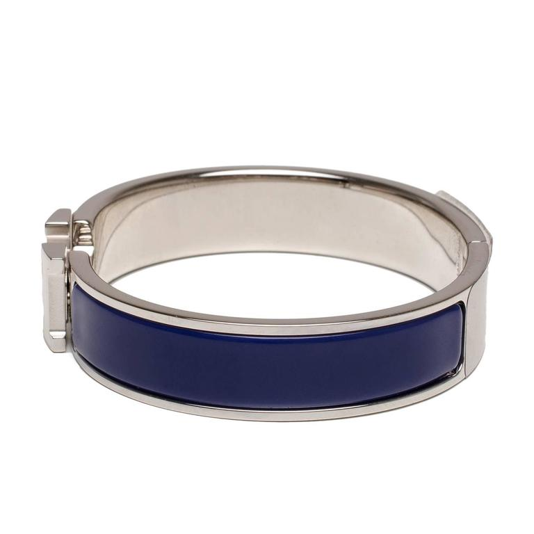 Hermes narrow Clic Clac H bracelet in blue enamel with a white enamel H closure and palladium plated hardware in size PM.  Origin: France  Condition: Pristine  Accompanied by: Hermes box, Hermes dustbag, Ribbon  Measurements: Diameter: