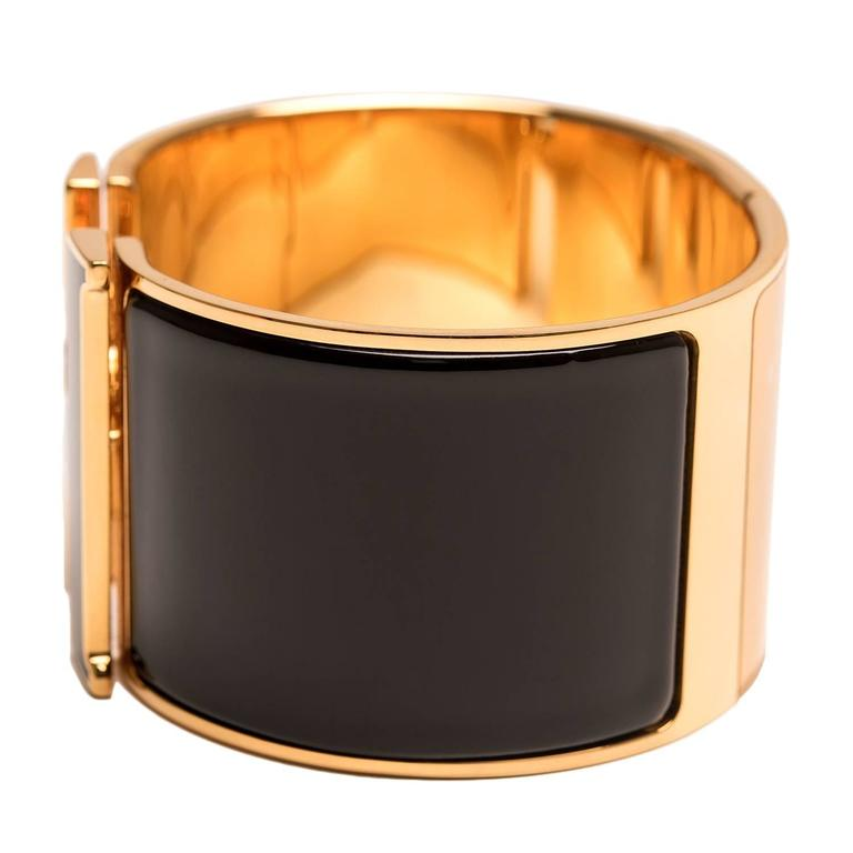 Hermes extra wide Clic Clac H bracelet in black enamel with black enamel H closure and gold plated hardware in size GM.  Origin: France  Condition: Never Carried  Accompanied by: Hermes box, Hermes dustbag, Ribbon  Measurements: Diameter: