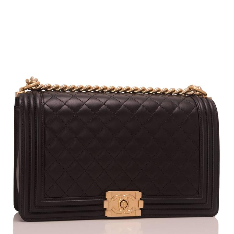 Chanel New Medium Boy bag of black lambskin leather with antique gold hardware.  This bag features a full front flap with the Le Boy CC push lock closure and an antique gold tone chain link and black leather padded shoulder/crossbody strap.  The