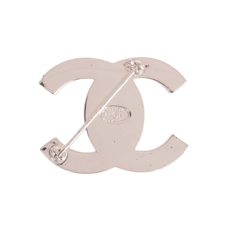 Chanel vintage silver tone rhinestone embedded CC-logo turnlock brooch.  Collection: 96A  Condition: Excellent  Accompaned By: Chanel box  Measurements: brooch width: 1.5in ; length 1in.