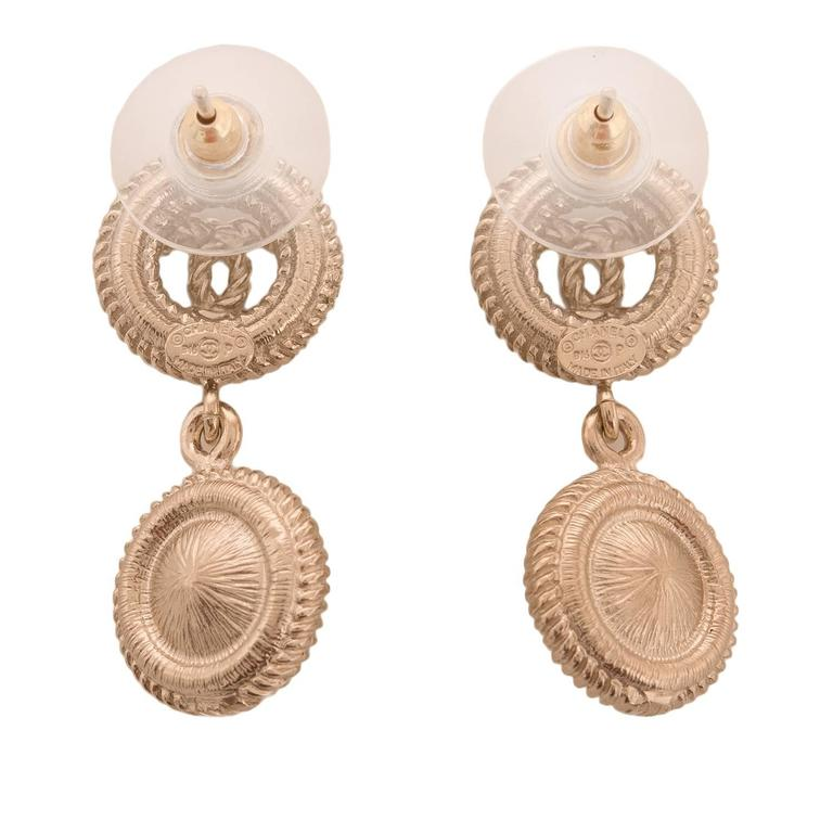 Chanel light gold tone baroque style drop pierced earrings of CC logo ear clips, and faux pearls and light gold drops.