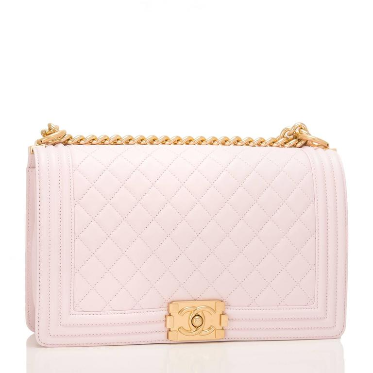 Chanel New Medium Boy bag of pink lambskin leather with antique gold tone hardware.  This bag features a full front flap with the Le Boy CC push lock closure and an antique gold tone chain link and pink leather padded shoulder/crossbody
