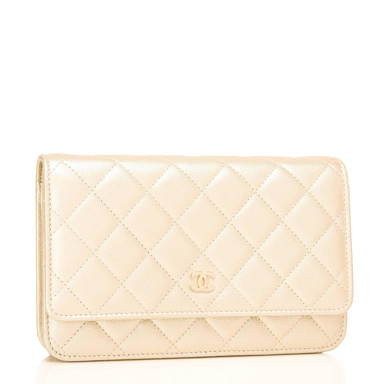 Chanel Classic Wallet on Chain (WOC) of gold caviar leather with gold tone hardware.  This Wallet On Chain features signature Chanel quilting, a front flap with CC charm and hidden snap closure, a half moon rear pocket and an interwoven gold tone
