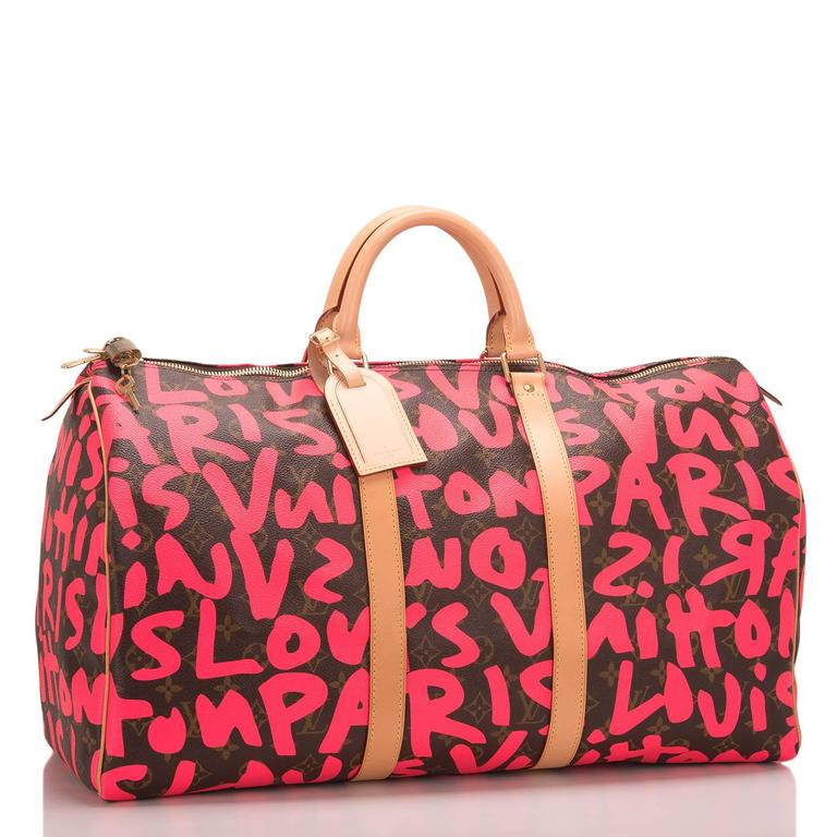 Louis Vuitton Pink Monogram Graffiti Keepall 50 of coated canvas with silk screened bright fluorescent pink colored graffiti lettering designed in tribute to Stephen Sprouse.