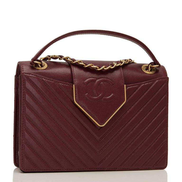 Chanel Paris In Rome burgundy quilted sheepskin flap bag with antique gold tone hardware.  This limited edition bag in a quilted chevron pattern with smooth leather on sides, top and bottom has front and back pockets, a front leather CC and gold
