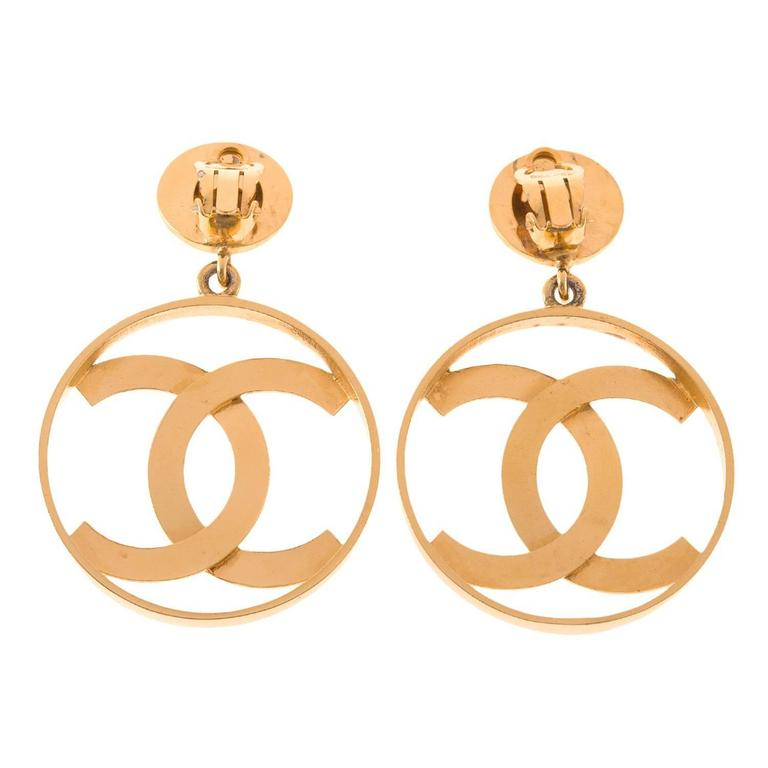 Chanel large vintage CC-logo hoop clip-on earrings of gold tone metal.  These rare earrings are large round hoops with Chanel's iconic CC-logos inside attached to disc earclips.   Collection: Vintage  Condition: Vintage; excellent. The gold